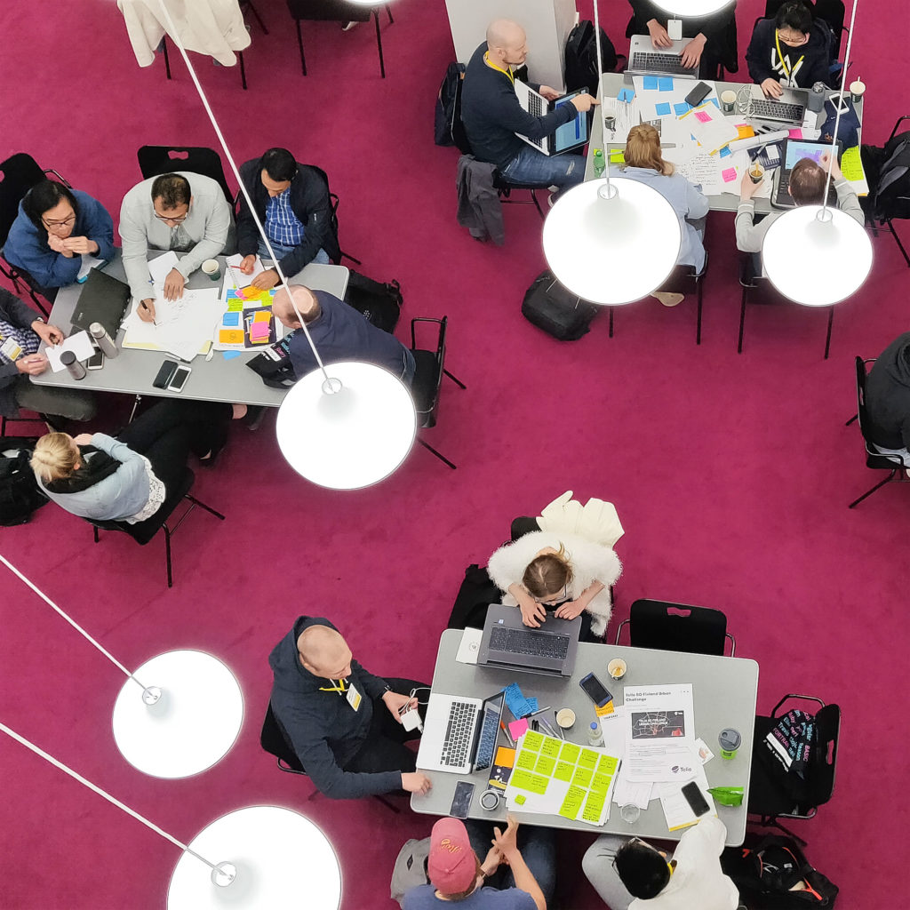 Top view of 3 groups of people ideating on tables.