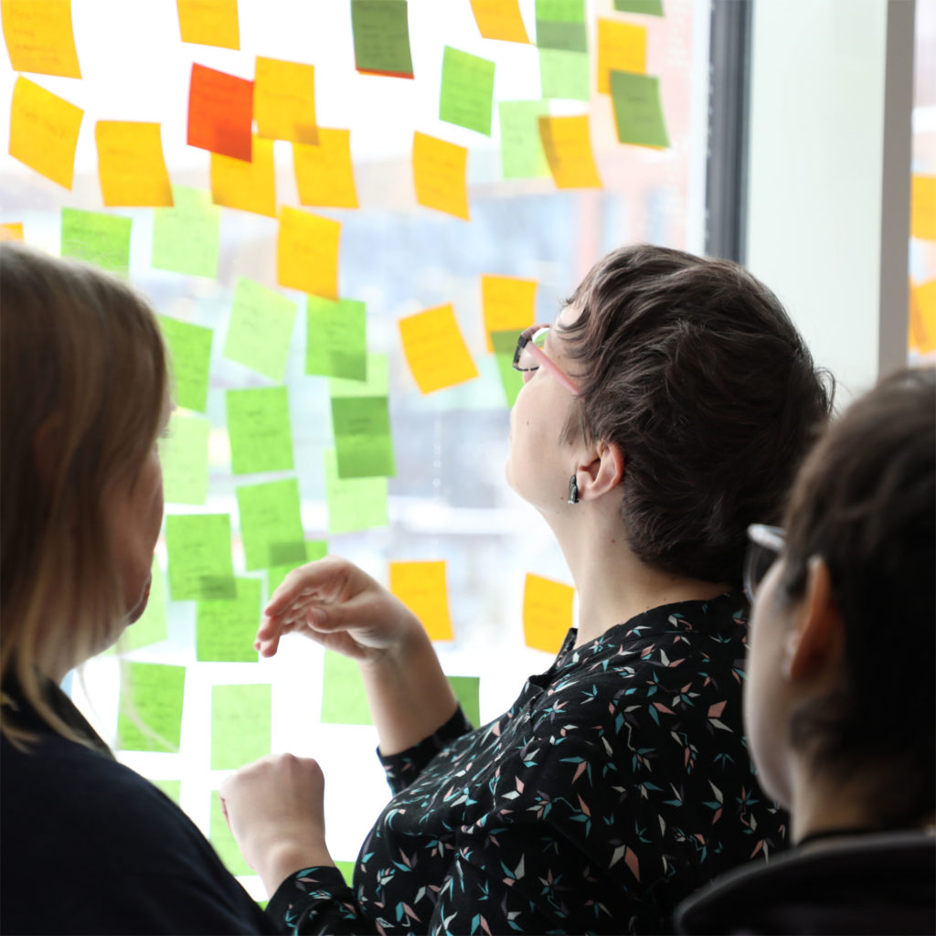 Group of teachers brainstorming with post-its on a glass wall.