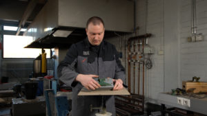 A man using an anvil mold in a workshop environment.
