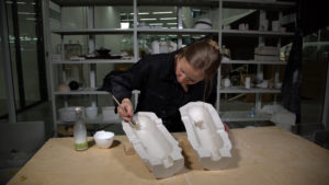 A designer creating a sculpture with plaster mold.
