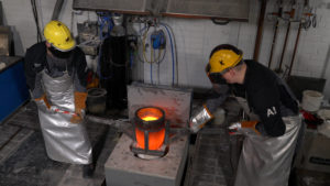 Two men casting metal.