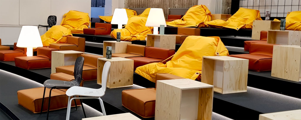A Grid Mordor-space lounge area with yellow fatboy chairs and white lamps.